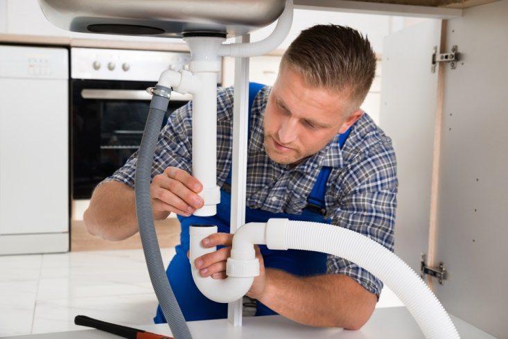 Man fixing pipe - Collins Plumbing, Gas & Heating